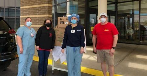 Two nurses and two CWA Local 2106 members in front of a hospital and donated lunches.
